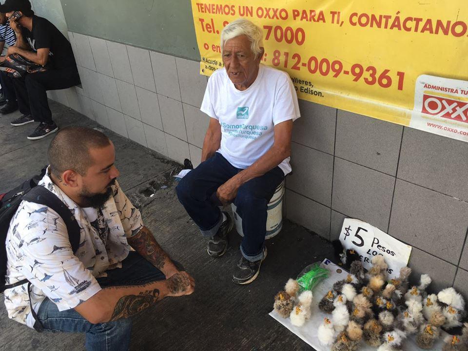 Luis Gameros platicando con un vendedor ambulante en le Centro de Monterrey. / FOTO: Cortesía